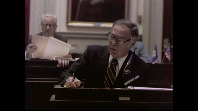 1970s: UNITED STATES: man takes notes at meeting. Man reads text to members at meeting