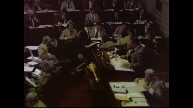 1970s: UNITED STATES: overhead view of members at meeting. People at meeting. Man speaks into microphone. Man holds microphone for colleague