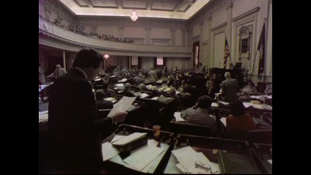 1970s: UNITED STATES: members gather in large room for meeting. Man sits in chair. Members look through papers. Lady sits in meeting
