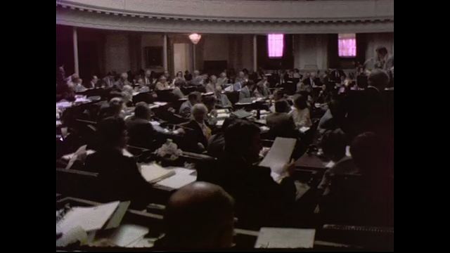 1970s: UNITED STATES: General Assembly members sit in meeting. Hands turn over pages in meeting.