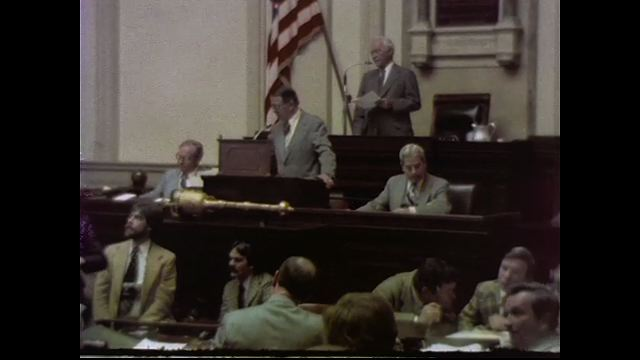 1970s: UNITED STATES: man stands by American flag at General Assembly meting. Exterior view of building