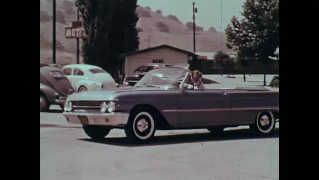 1960s: Woman driving, backs out of parking space. Foot on pedal. Close up, woman driving.