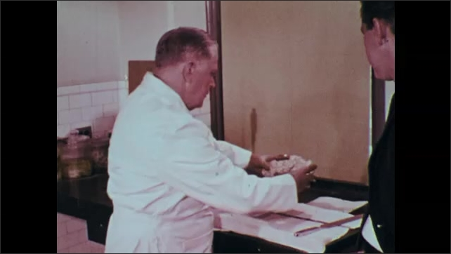 1960s: Hands touch pieces of brain on table. Close up, man talking. Man sets down segments of brain, takes brain from sink.