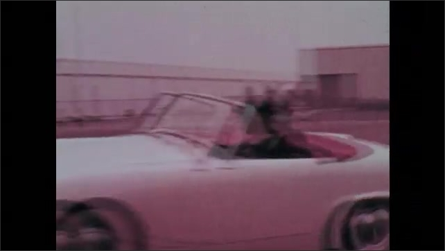 1960s: Men sitting in auditorium. Tracking shot from car, driving through course in parking lot. Cars driving through course. Pan across men in cars.
