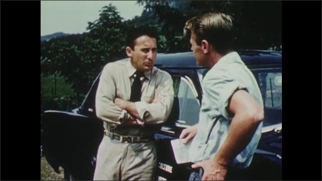 1950s: Two men stand by car, talk.