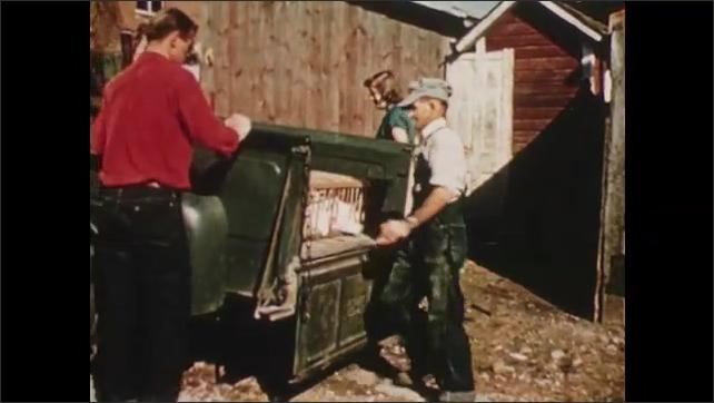 1950s: Men put crate of chickens in truck, man puts in bag, men close tailgate.