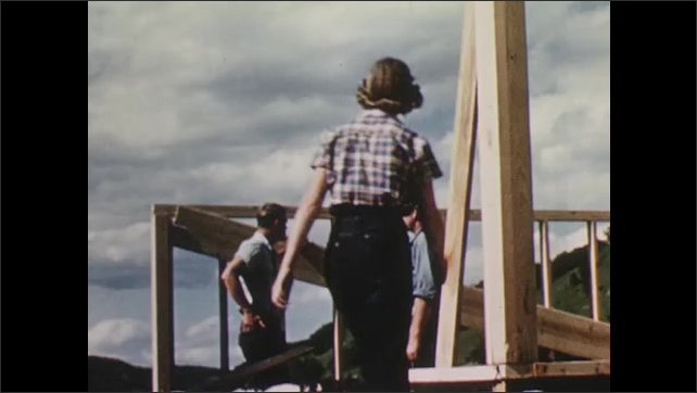 1950s: Man cleaning in barn. Sprayer washing crates. Men talking on construction site, woman enters.