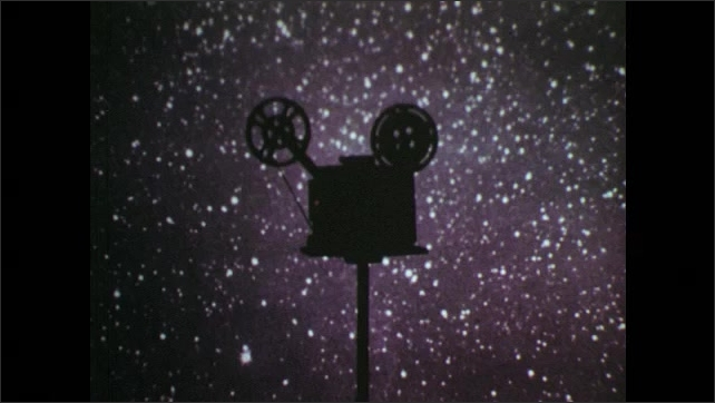 1970s: Drive belts move inside open 16mm projector. Multiple numbers flash and overlap each other. A 16mm projector stands on a table and runs in the dark, is illuminated, stars in background.