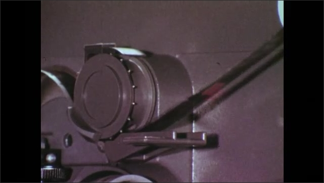 1970s: Hand holds filmstrip in a projector and points with a pencil at film's perforation, projector starts to run, film runs through the projector.