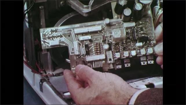 1970s: Screw driver unfastens screw from circuit board. Hand removes circuit board and shows it. Hand shows piece of film shutter mechanism from a film projector.