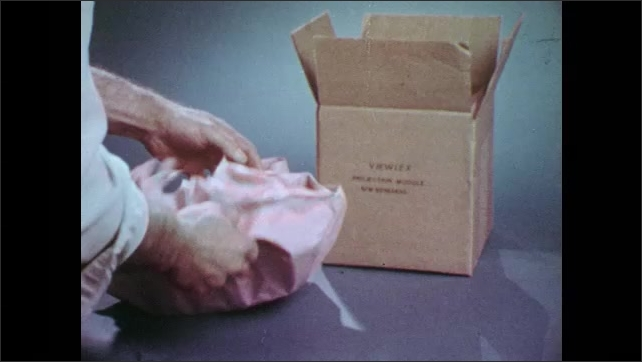 1970s: Text ????iewlex projection Module????printed on a cardboard box, hands unwrap projection module and show it.