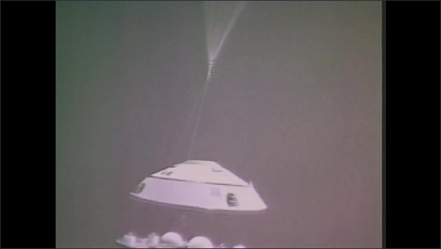 1970s: Parachute opens over space craft. Vehicle drops from parachute.