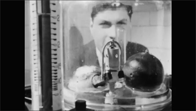 1950s: Machine lifts. Weights bob in glass with liquid. Girl speaks. Man talks.