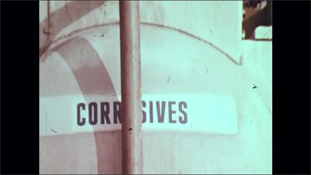 1970s: Person in hazardous material suit stands on ledge in factory above vat with the word: Corrosives, on it. Sign on vehicle says: Corrosives.