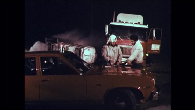 1970s: Man looks at pamphlet on how to handle Oleum. Two men stand by car and wrecked truck at night, talking. Two men walk around wrecked truck.