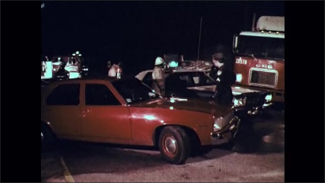 1970s: Police officers and firemen talk to each other at scene of truck accident at night. Police car drives away.