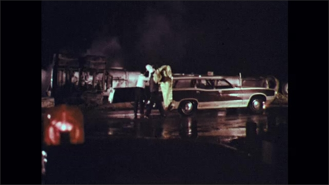 1970s: Car pulls up to scene of accident at night. Men in hardhats get out of car. Men pull hazardous material suits from back of car.