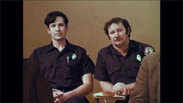 1970s: Man in uniform talks in front of classroom of adults, including police officers. Adults in classroom listen to man talk.