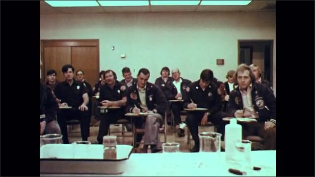 1970s: Firemen in protective gear spray protective foam material on wrecked tanker. Adults and police officers sit in classroom.