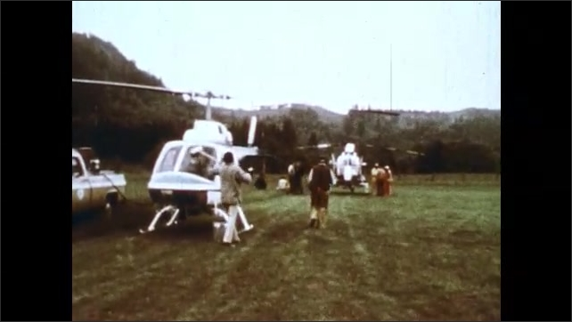1980s: Still image of smoke/ash (?). Pickup truck and helicopters parked in field, man washes helicopter windows. Obliterated forest on side of mountain after Mt St Helens eruption.