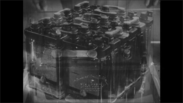 1940s: Voltaic cells are inside glass containers. Hands open caps from a lead-acid battery, take a hydrometer that lays on the table and shows it with both hands.