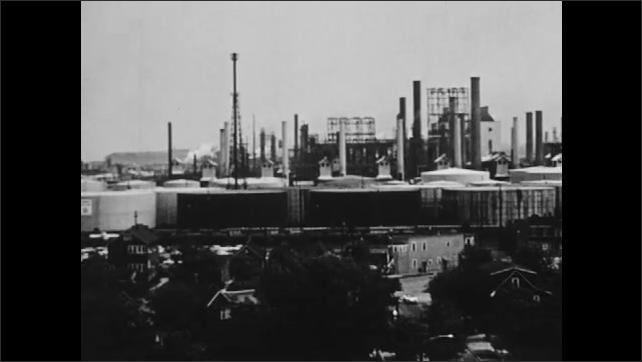 1960s: Dense houses, trees leading up to industrial area, factories, smoke stacks, storage tanks.