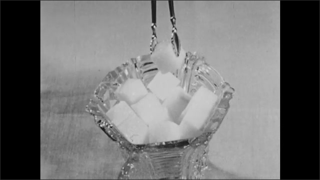 1960s: Industrial storage tanks, stairs. Factories, smoke stacks. People walk by buildings. Tongs pick up sugar cube, ice cube, place in drink. Yard, pitcher, hand stirs drink with striped straw.