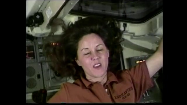 1990s: Woman floats in space capsule, looks out window, talks. Earth's atmosphere. Space shuttle under construction in hangar.