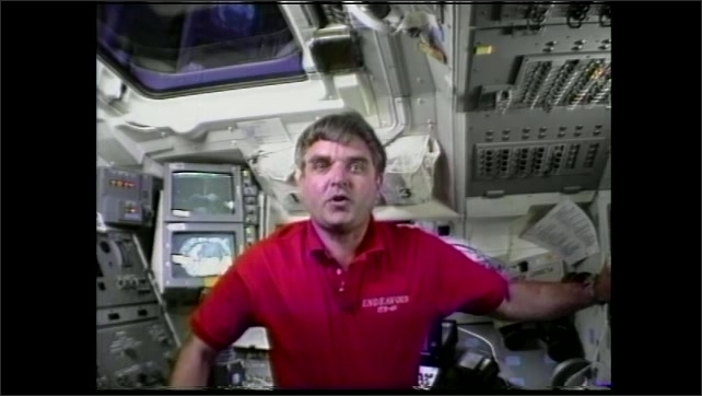 1990s: Satellite outside window of space shuttle. Man floats in space shuttle, talks. Aerial image of earth.