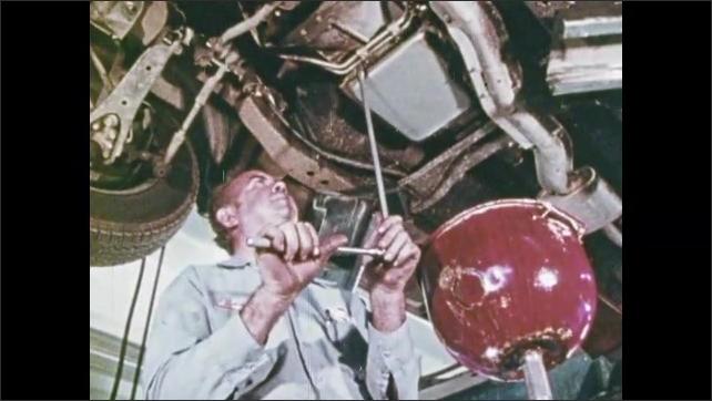 1970s: Woman rolls down car window.  Control panel.  Garage.  Mechanic works on car.  Man adds oil to engine.