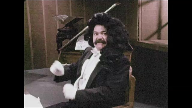 1970s: Man in period costume and wig sits in chair and speaks. Man in period costume writes at desk with feather quill.