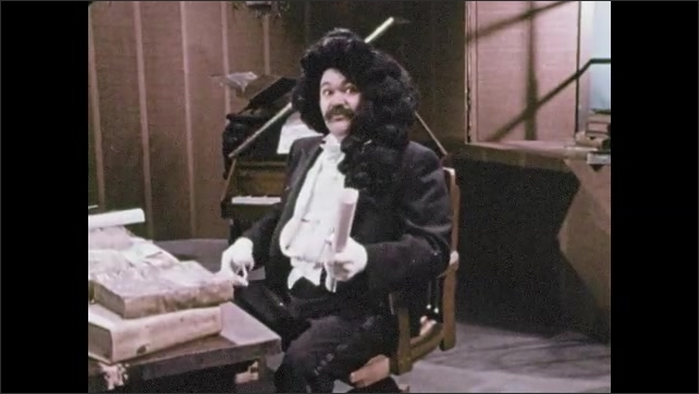 1970s: Man in period garb gathers scrolls from desk and speaks.