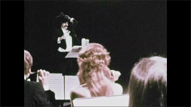 1970s: Maestro conducts at stand with toothbrush. Conductor bows and orchestra rises from chairs.