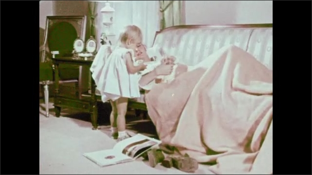 1970s: Man talks. Child stands in living room, cries. Woman lays on couch, child walks away from woman. Child sits on floor, cuts paper, woman sits on couch.