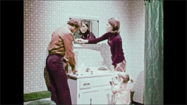 1970s: Man and woman go through medicine cabinet. Child stands near bathroom sink, goes through drawers.