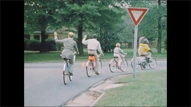 1970s: UNITED STATES: yield sign by road. Boy rides bike. Family signal with hands on bikes. Stop sign. Man works in garden