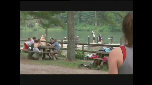 1990s: Kids ride boat through rapids.  Boy and girl walk through picnic grounds, talk to each other.