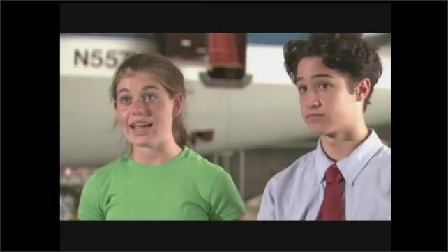 1990s: Boy and girl walk through airplane hangar, talk with man.