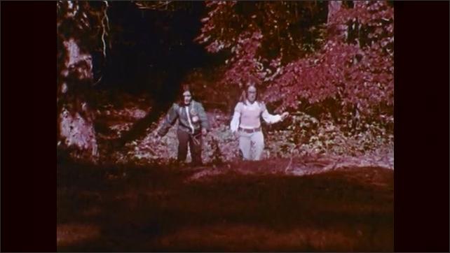 1970s: Two girls walk through woods.