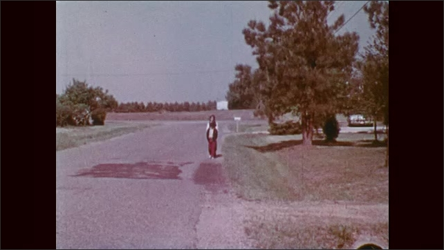1970s: Boy adjusts bicycle tire behind parked car. Kids walk in single file on side of road.