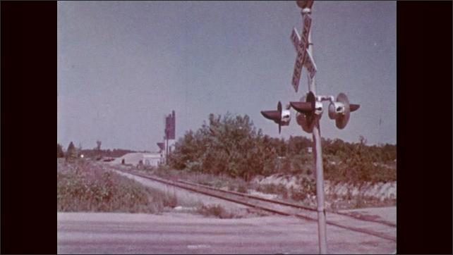1970s: Boy exits bus, walks on grass next to street. Kids walk up to railroad tracks, stop, look around.