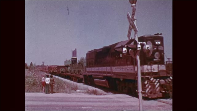 1970s: Train signal flashes. Kids wait on side of the road in front of railroad tracks, train comes down tracks. Kids wait for train to pass.