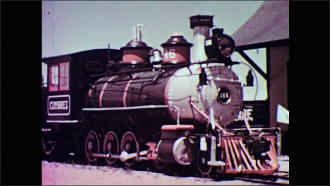 1950s: Front of train engine. View of train engine. Pan across train wheels.