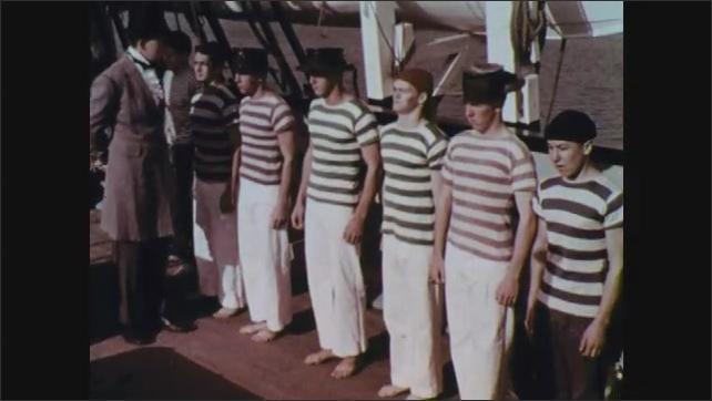 1960s: Man climbs ladder onto boat. Man talking, man's shoulder in foreground. Man walks past men in line, pulls men forward.