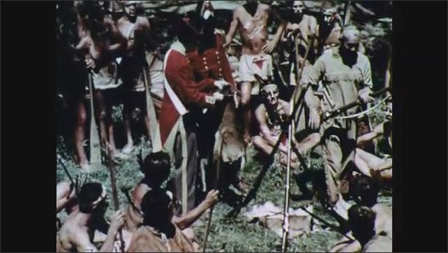 1960s: Man trades gun for fur with native man. Close up of man. Man talking.