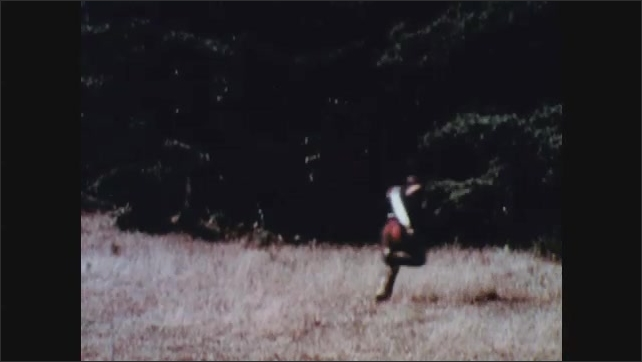 1960s: Men standing by river. Man leading group of men. Men walking. Man talks to group. Men running. Men run to woods. Man fires gun, Man falls. Men running. Man on ground. Men running.