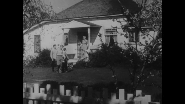 1950s: Farmer observes flower blossoms on tree branch. Boys wave to woman on porch of house. Woman hands lunchbox to boy. Boy kisses woman and runs from porch.