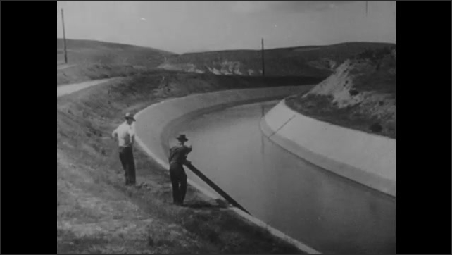 1950s: Water runs along channel at dam. Water rolls down irrigation channel through mountains. Men turn crank at irrigation channel. Water runs down gully in dirt.