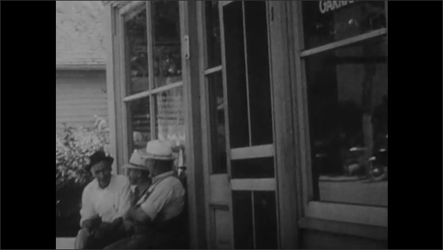 1950s: Farmer places onion in basket in field. Men sit on bench near post office. Man removes mail from mailbox.