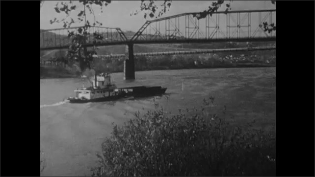 1950s: Corn waves in fields. Steamboat paddles up river near bridge. Ship enters bay beneath iron gate.